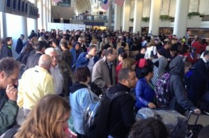 Stranded American Airlines passengers queue for information today.