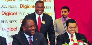 Digicel manager Alex Tasker (standing left) shares a joke with Minister Donville Inniss and other officials at today's ceremony.