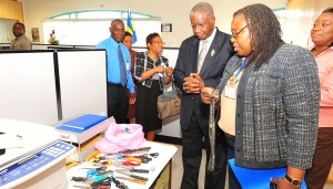 Prime Minister Freundel Stuart examines confiscated weapons in the presence of Chief Welfare Officer, Patricia Watts.