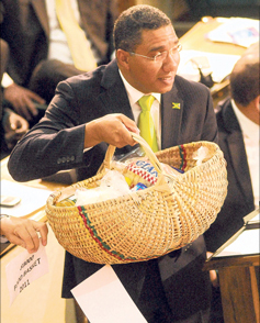 Opposition Leader Andrew Holness displays one of two food baskets he used in the Parliament yesterday to demonstrate the sharp rise in the cost of living.