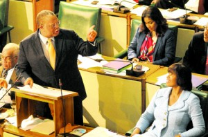 Finance Minister Dr. Peter Phillips speaking as he opens the Budget debate in Parliament yesterday. At right is Prime Minister Portia Simpson Miller.