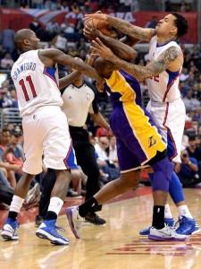 Clippers' forward Matt Barnes (right) and guard Jordan Crawford smother Lakers forward Earl Clark during last night's win.