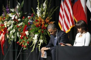 US President Barack Obama and wife Michelle bow their heads during yesterday's memorial service.
