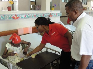 Digicel Retail Sales Executive, Yasmine Millington (centre) assists one of the very lively and cheerful Geriatric Hospital patients with her package. Looking on is Digicel's Commercial Director, Alex Tasker (right).