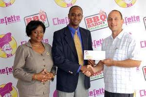 Devrol Dupigny (centre) receiving the cheque from Chefette's Ryan Haloute while Lisa Carter looks on.