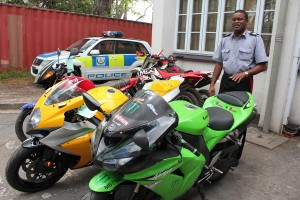 Station Sergeant Rodney Inniss with some of the big bikes seized.