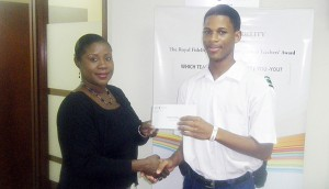 Trust administrator at Royal Fidelity Gail Walters presents Christopher derell with his winnings.