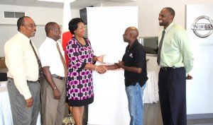 Receiving the cheque from Catherine Leslie (third left) was head of the Warrens committee Adrian Harewood (second right). Looking on at left is Courtesy's regional product manager Samuel Gaston, Roger Maxwell, sales manager for Nisan and president of Warrens Sports Club Peter Alleyne (right).