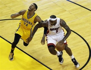Heat's LeBron James (with ball) drives past Pacers' Paul George for the game-winning basket.