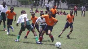Zavier Marshall of Eagle Hall Primary skilfully eludes this tackle from Trinity's Jai Alleyne.