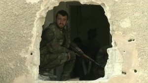 A Syrian rebel takes up position in an abandoned building in Damascus.