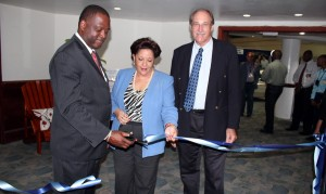 Minister Donville Inniss (left) and BMA Executive Director Bobbi McKay cut the ribbon to open BMEX 2013, while President David Foster looks on.