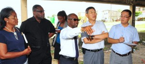 Minister of Youth, Stephen Lashley showing Wu Gangchen areas to be renovated.