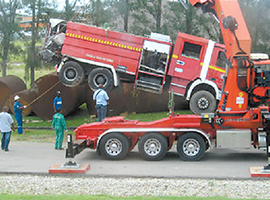 A truck-mounted crane lifts the damaged firetruck off the flatbed tow truck on the Junior Sammy compound.