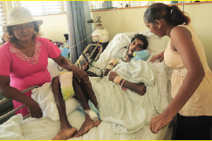 The family of stricken Ryan Rampersad, centre, yesterday at the Port of Spain General Hospital. At right is his wife Sally Ann Rampersad and his grandmother Verro James.