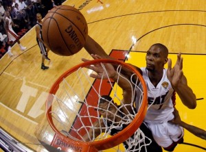 Heat's Chris Bosh tips the ball back for two points over the Spurs' Tim Duncan.