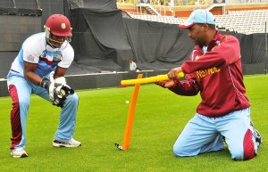 Johnson Charles (left) today going through some drills prior to his wicketkeeping duties tomorrow.