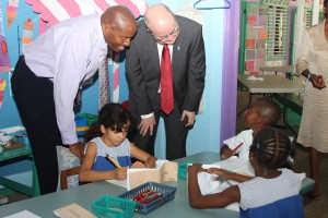 Can I see what you have there? - British High Commissioner Paul Brummell as well as Football Coach Alfred John reviewing the work of students in Infants T class.
