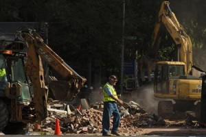 Men work at the scene of the building collapse.