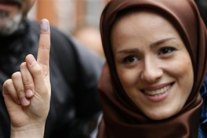 Voter Zeynab shows the ink stain on her finger, to prove that she has voted, outside the Iranian consulate in central London