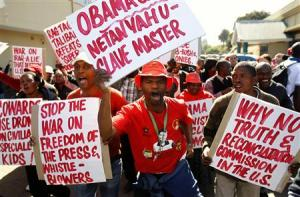 Protesters carry placards as they protest against the visit of U.S. President Obama in Pretoria