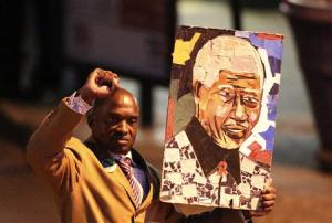 A well-wisher carries a portrait of former South African President Nelson Mandela outside the Pretoria hospital where former President Mandela is being treated