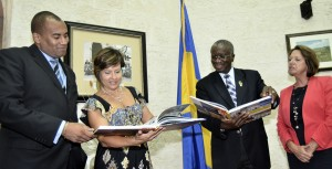 Minister of Tourism Richard Sealy (left), President of the BHTA, Patricia Affonso- Dass, Prime Minister Freundel Stuart and BHTA Executive Vice-President, Sue Springer, looking through the book which captures Barbados' tourism heritage