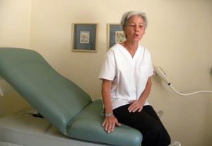 Clinic Co-ordinator, Sister Sian Monteith, sits on the new medical couch in the cervical cancer detection section.