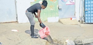 A worker empties a bucket of sewage mopped up from the floor of one of the stores on West Street, downtown Kingston, that were forced to closed because of overflowing sewage in the area, yesterday.