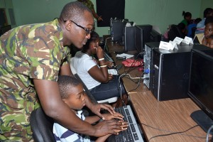 de of army Private David Maynard giving guidance to one of the children.
