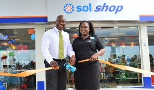 Sol Country Manager, Ezra Prescod and retailer, Tonya Trotman cutting the ribbon to declare the service station open.
