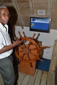 Museum manager Sampson behind the wheel of a virtual ship on the Wharf Memories floor.