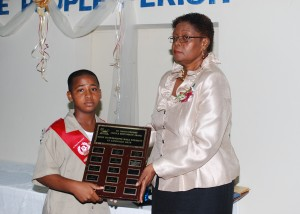 Principal, Linda Archer presenting valedictorian Tyreke Goddard with his plaque for outstanding academic achievements.