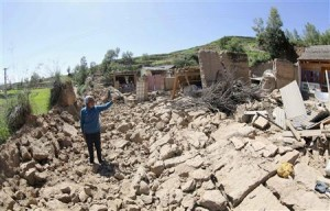 A woman points at her collapsed home after a 6.6 magnitude earthquake hit Minxian county