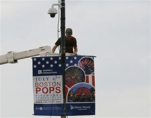 A worker installs a piece of security equipment on a lamp post on a bridge over the Charles River in Boston