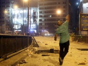 A supporter of deposed Egyptian President Mohamed Mursi throws stones at riot police during clashes in the Ramsis square area in central Cairo