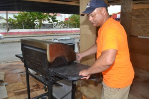 Tent assistant and Bartender Gregory Goodridge removing a grill from the stall.
