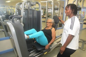 Icilma Marsh doing her leg presses under the watchful eye of her personal trainer Anita Husbands.