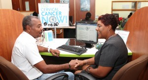 Customers at the Sagicor Life Inc Belleville Branch sign the e-petition to join the fight against cervical cancer.