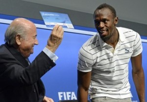 Sepp Blatter (left) presenting Usain Bolt with his 2014 World Cup Football ticket.