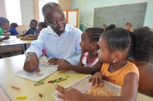 """Minister of Youth Stephen Lashley demonstrated today that he still """"has the touch"""" when he won heart after heart while touring Government summer camps. Here he's all smiles with Jasmine Brathwaite at the Vauxhall Primary camp, while Victorial Rayside looks on."""
