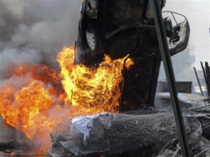 A vehicle burns at the scene of a car bomb attack in Baghdad's Kadhimiya district