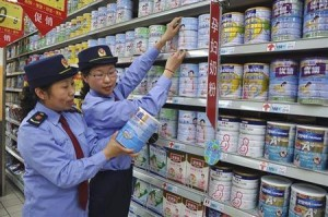 Chinese commercial law enforcement personnel inspect milk powder products at a supermarket in Lianyungang