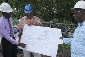 Senior Draughtsman Andrew Parris (left) points out the feature of the new academy at Erdiston, while contractor with CRS Building and Maintenance, Sydney Blenman and Minister Jones look on.
