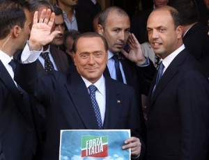 Silvio Berlusconi waves to supporters next to People of Freedom (PDL) Secretary Angelino Alfano (ight) while showing the logo of his re-launched political party, Forza Italia (Go Italy), in downtown Rome today.