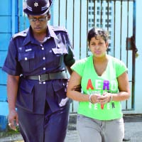 Trinidad - Alicia Acevero, 21, is escorted to the Sangre Grande Magistrates' Court yesterday charged with killing her two-day-old baby Nishan Lal
