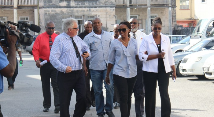 "Publisher of the Nation newspaper, Vivian-Anne Gittens (in white jacket), senior journalist Sanka Price (walking behind her) and Editor-in-Chief Roy Morris (in back, wearing black) being led to the District ""A"" Court to answer the charges. At left is Queen's Counsel Alair Shepherd who is leading the Nation's defence team."