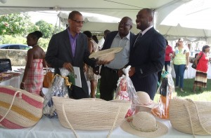 Permanent Secretary in the Barbados Ministry of Foreign Affairs, Charles Burnett (left), favours a straw hat  on exhibition. At centre is  Guyana Consul General, Michael Brotherson, and at right is Guyana Go-Invest Officer, Shawn Doris.