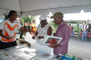 Manager of Sapphire Batik Creations, Louise Jordan (left) explains pieces of her work to Patron of the Festival, Monica Drayton, wife of Central Bank Governor, Delisle Worrell who is at right.