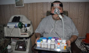 Hadyn Chandler, wearing his oxygen mask, holding the 42 different medications he has to take every day.